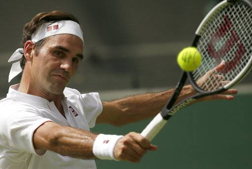 Roger Federer of Switzerland returns the ball to France's Adrian Mannarino during their men's singles match, on day seven of the Wimbledon Tennis Championships, in London, Monday July 9, 2018.