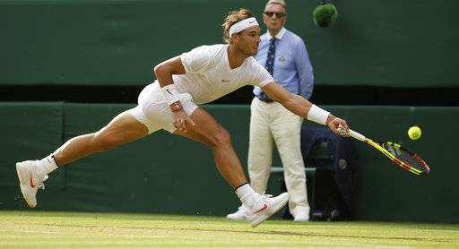 Rafael Nadal of Spain returns the ball to Czech Republic's Jiri Vesely during their men's singles match, on day seven of the Wimbledon Tennis Championships, in London, Monday July 9, 2018.