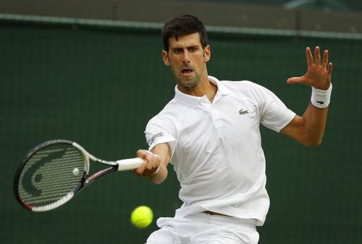 Novak Djokovic of Serbia returns the ball to Karen Khachanov of Russia during their men's singles match on the seventh day at the Wimbledon Tennis Championships in London, Monday July 9, 2018.