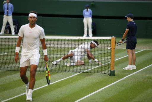 Juan Martin Del Potro of Argentina, right, slips on the grass during the men's quarterfinal match against Rafael Nadal of Spain at the Wimbledon Tennis Championships in London, Wednesday July 11, 2018.