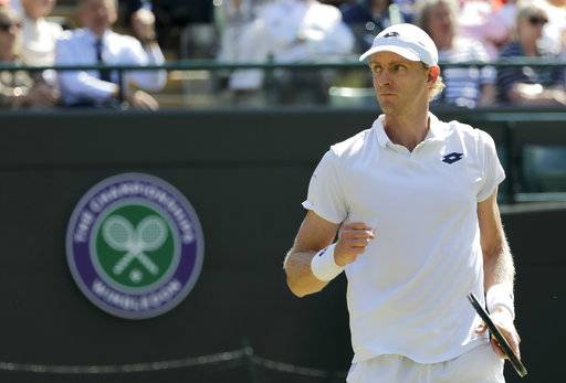 Kevin Anderson of South Africa celebrates breaking serve in his men's quarterfinals match against Switzerland's Roger Federer, at the Wimbledon Tennis Championships, in London, Wednesday July 11, 2018.