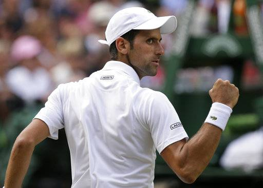 Novak Djokovic of Serbia celebrates breaking the serve of Kei Nishikori of Japan during their men's quarterfinal match at the Wimbledon Tennis Championships in London, Wednesday July 11, 2018.