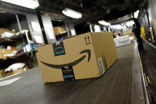 FILE- In this May 9, 2017, file photo, a package from Amazon Prime moves on a conveyor belt at a UPS facility in New York. Amazon's Prime Day starts July 16, 2018, and will be six hours longer than last year's and will launch new products.