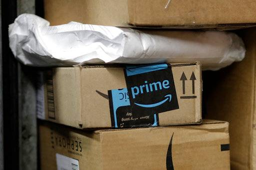 FILE- In this May 9, 2017, file photo, a package from Amazon Prime is loaded for delivery in New York.  Amazon's Prime Day starts July 16, 2018, and will be six hours longer than last year's and will launch new products.