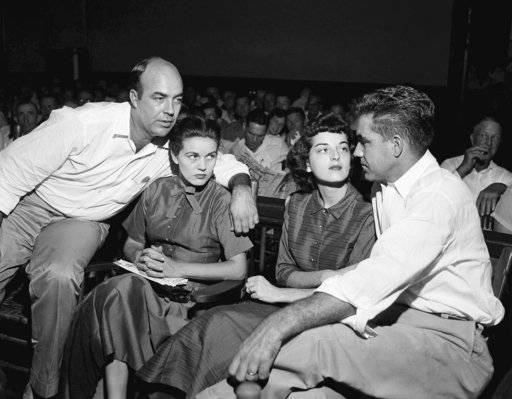 "FILE - In this Sept. 23, 1955, file photo, J.W. Milam, left, his wife, second left, Roy Bryant, far right, and his wife, Carolyn Bryant, sit together in a courtroom in Sumner, Miss. Bryant and his half-brother Milam were charged with murder but acquitted in the kidnap-torture slaying of 14-year-old black teen Emmett Till in 1955 after he allegedly whistled at Carolyn Bryant. The men later confessed in a magazine interview but weren't retried; both are now dead. Citing ""new information,"" the U.S. Justice Department has reopened the investigation into Till's death."