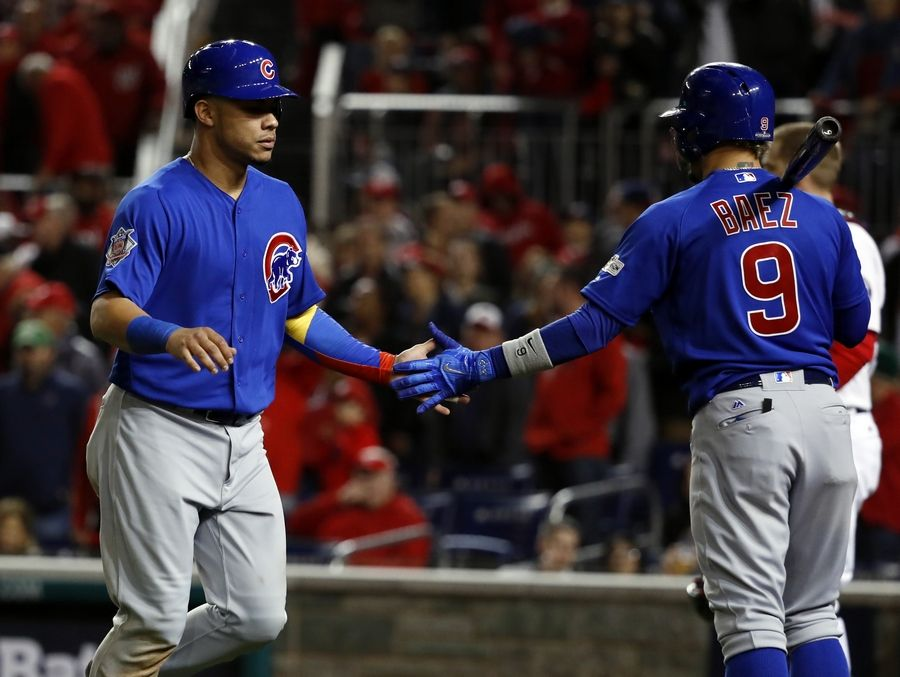Cubs catcher Willson Contreras is congratulated by infielder Javier Baez after scoring on a wild pitch during the third inning of Game 5 the the NLDS last October. Much as baseball is passed from generation from generation, there are many hands who have helped in the development in Cubs all-stars Baez and Contreras