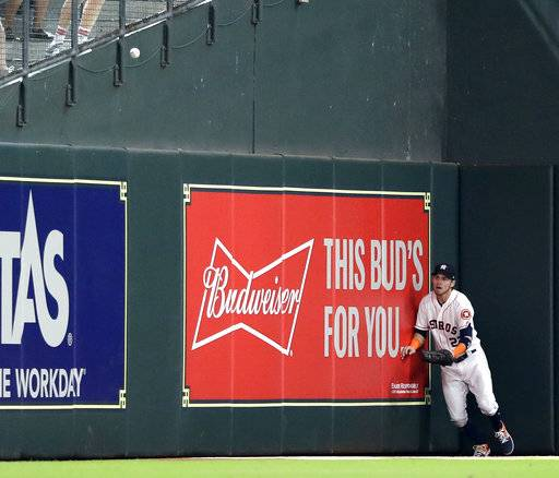 Houston Astros left fielder Josh Reddick chases a two-run double by Oakland Athletics' Mark Canha during the eighth inning of a baseball game Thursday, July 12, 2018, in Houston.