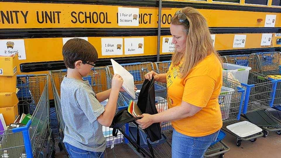 "Golfview Elementary Principal Lindsay Sharp helps a student fill a backpack with school supplies during the 2016 District 300 ""Stuff the Bus"" event."