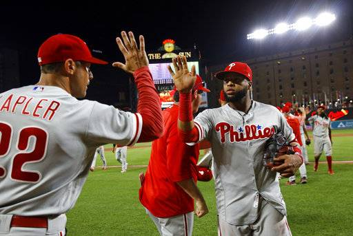 Philadelphia Phillies' Carlos Santana, right, high-fives manager Gabe Kapler after the team's baseball game against the Baltimore Orioles, Thursday, July 12, 2018, in Baltimore. Philadelphia won 5-4.