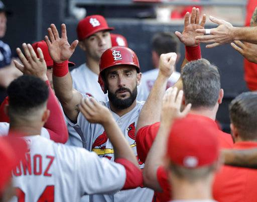 St. Louis Cardinals' Matt Carpenter celebrates in the dugout after scoring on a single by Jose Martinez during the third inning of a baseball game against the Chicago White Sox Tuesday, July 10, 2018, in Chicago.