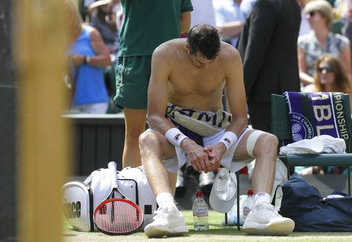 John Isner of the United States sits after losing the first set in his men's singles semifinals match against South Africa's Kevin Anderson, at the Wimbledon Tennis Championships, in London, Friday July 13, 2018.