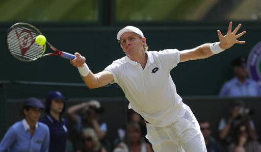 South Africa's Kevin Anderson returns the ball to John Isner of the United States during their men's singles semifinals match at the Wimbledon Tennis Championships, in London, Friday July 13, 2018.