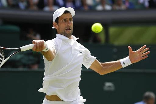 Novak Djokovic of Serbia returns the ball to Kei Nishikori of Japan during their men's quarterfinal match at the Wimbledon Tennis Championships in London, Wednesday July 11, 2018.