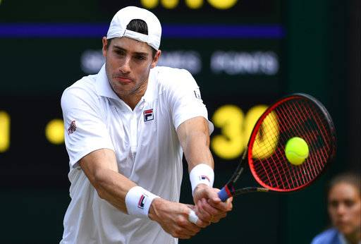 John Isner of the US returns a ball to Kevin Anderson of South Africa during their men's singles semifinal match at the Wimbledon Tennis Championships, in London, Friday July 13, 2018.