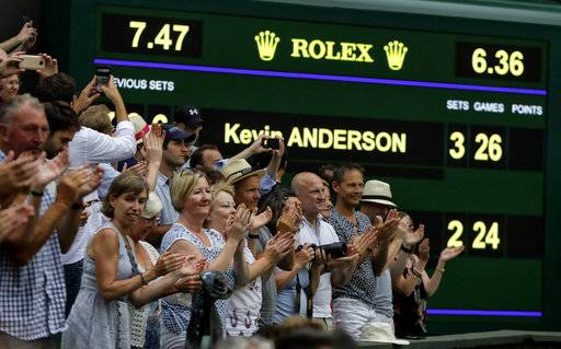 Spectators applaud as the scoreboard displays the final score in the men's singles semifinals match in which John Isner of the United States was defeated by South Africa's Kevin Anderson, at the Wimbledon Tennis Championships, in London, Friday July 13, 2018.