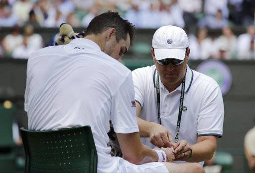 John Isner of the US receives medical treatment on court during the men's semifinal match against Kevin Anderson of South Africa at the Wimbledon Tennis Championships in London, Friday July 13, 2018.