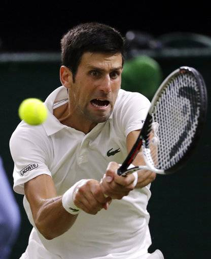 Novak Djokovic of Serbia returns a ball to Rafael Nadal of Spain during the men's semifinal match at the Wimbledon Tennis Championships in London, Friday July 13, 2018.