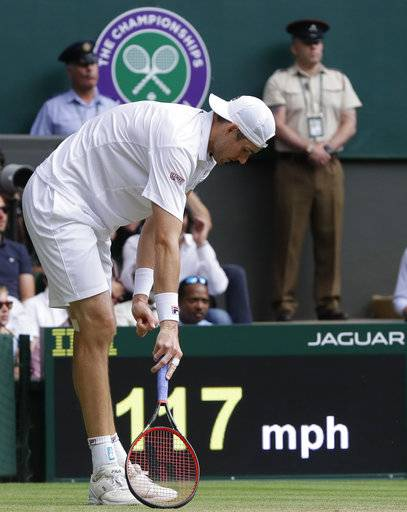 John Isner of the United States pauses after stumbling as he returned the ball to South Africa's Kevin Anderson during their men's singles semifinals match at the Wimbledon Tennis Championships, in London, Friday July 13, 2018.