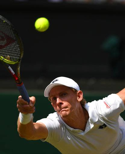 Kevin Anderson of South Africa returns a ball to John Isner of the US during their men's singles semifinal match at the Wimbledon Tennis Championships, in London, Friday July 13, 2018.