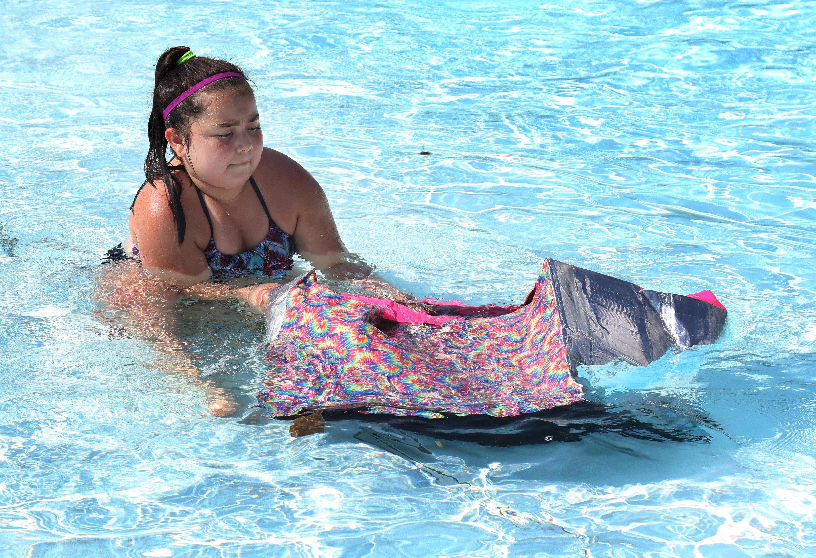 "Clairianah Medina, 11, of Carol Stream tries to lift her boat out of the water Sunday after it sank during the ""Sink or Swim Boat Challenge"" at the Bartlett Aquatic Center."