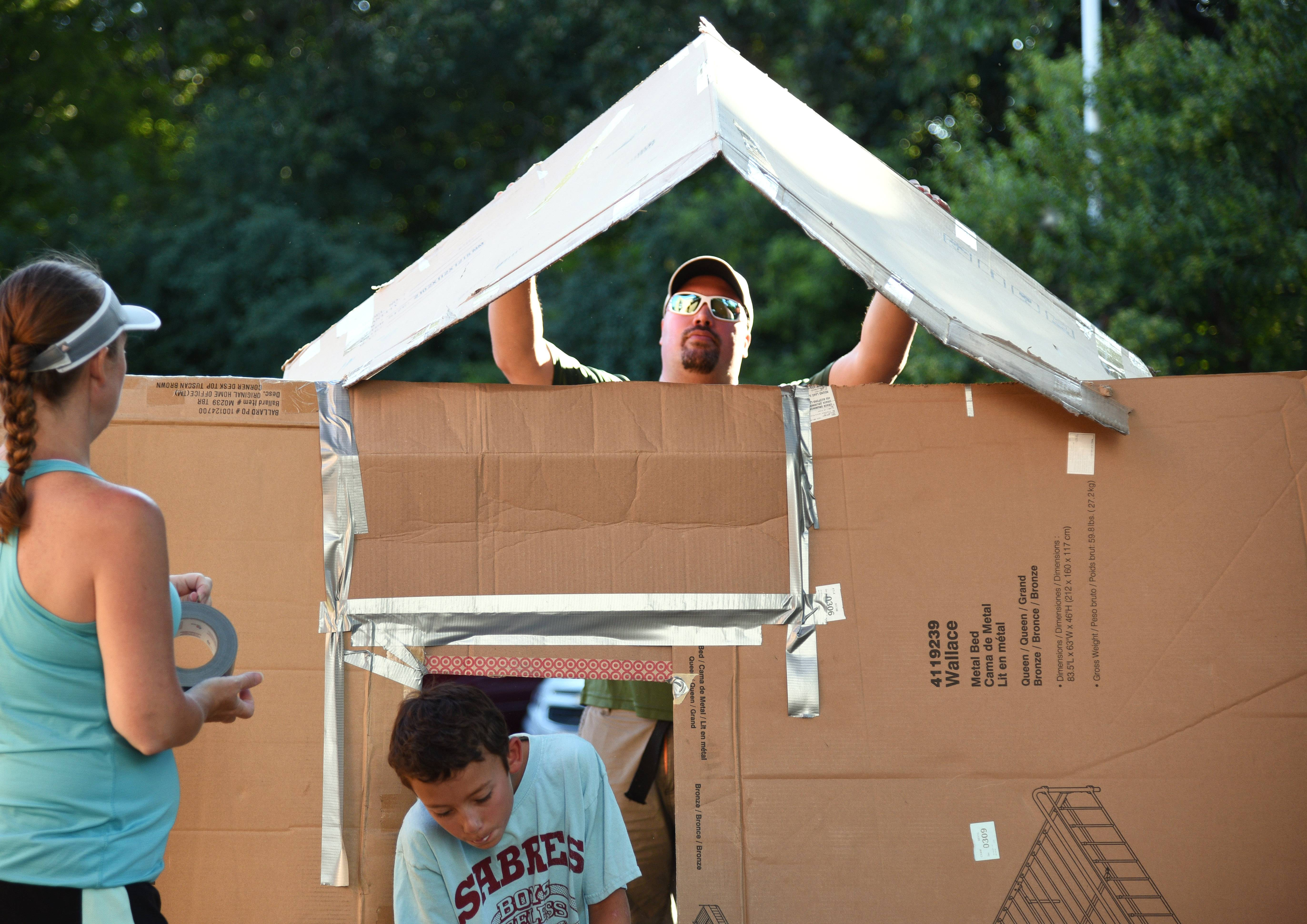 Matt Hoffman of Wauconda sets the roof in place as his wife, Janet, and son, Trevor, tend to the duct tape during Monday nights's Second Annual Family Fort Build at the Wauconda Area Library.