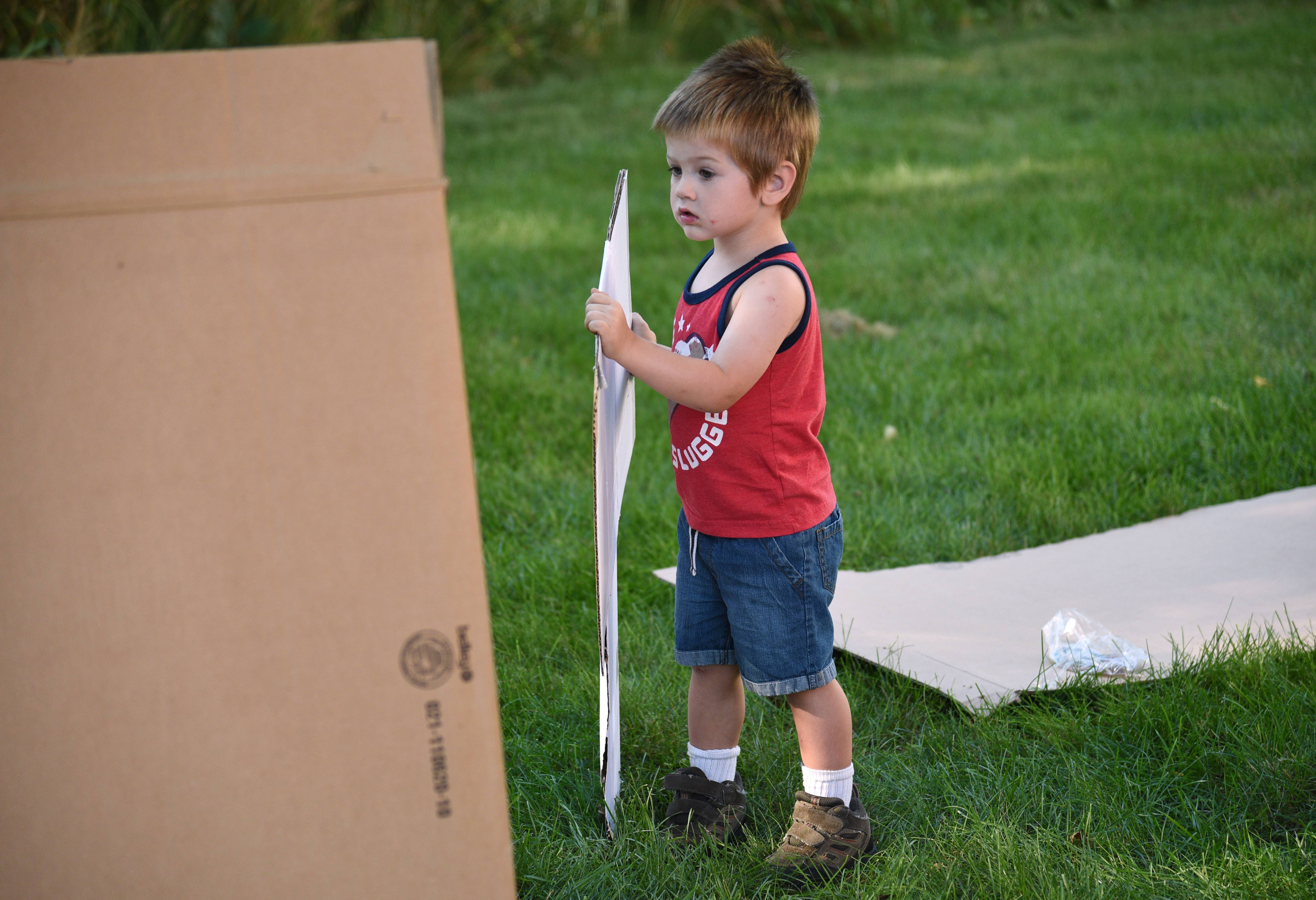 Two-year-old Benny Rebmann of Wauconda lends his family a hand during Monday nights's Second Annual Family Fort Build at the Wauconda Area Library.