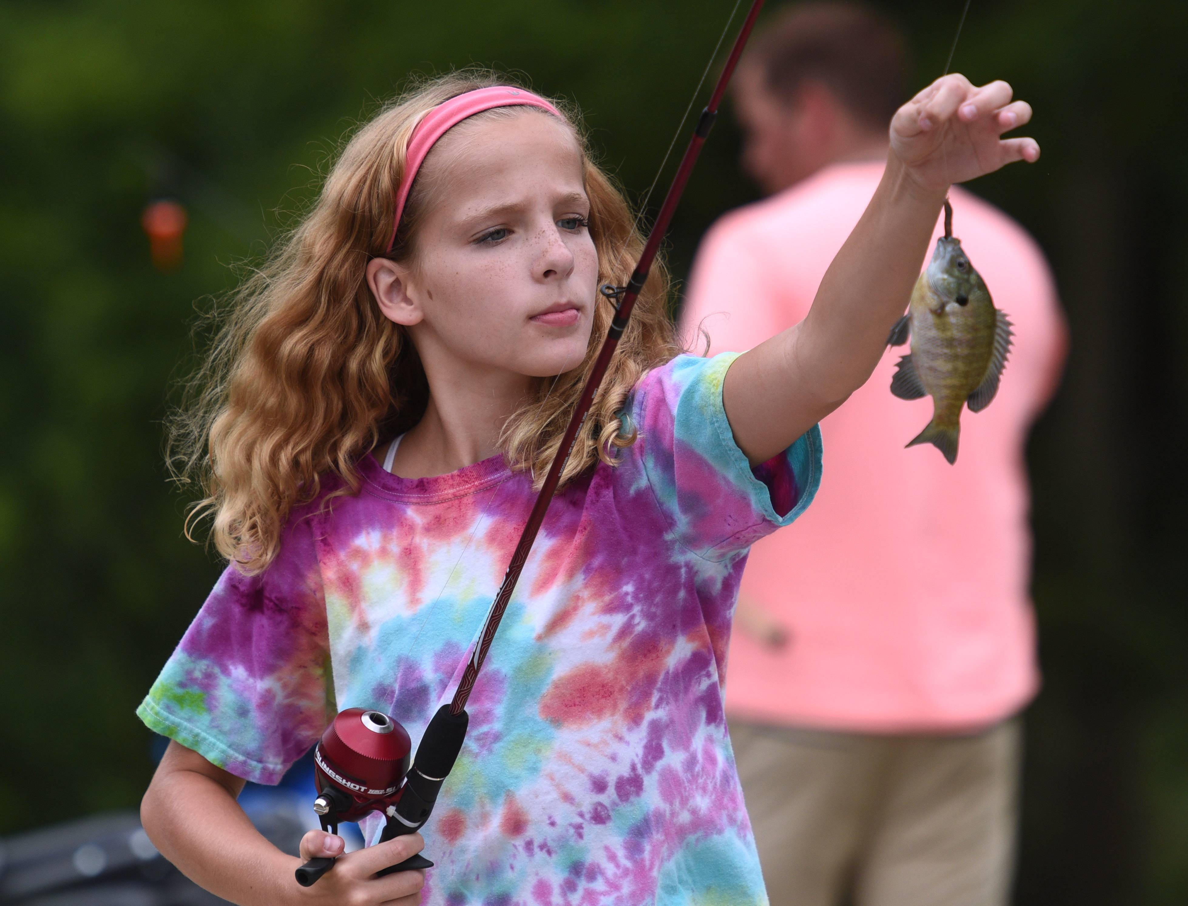 Alison Bogenski, 12 of Mundelein, takes a fish she caught to get weighed in during the Mundelein Police Department's 21st Annual Cops 'N' Bobbers fishing derby Saturday at the University of Saint Mary of the Lake seminary.