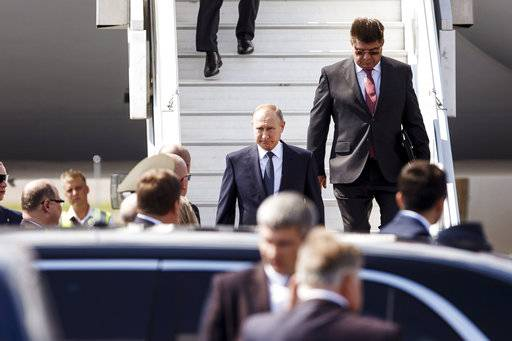 Russia's new ambassador to Finland Pavel Kuznetsov, background righ escorts Russian President Vladimir Putin as he disembarks the plane at Helsinki airport in Vantaa, Finland, Monday, July 16, 2018. Putin arrived for his summit with US President Donald Trump. (Roni Rekomaa/Lehtikuva via AP)