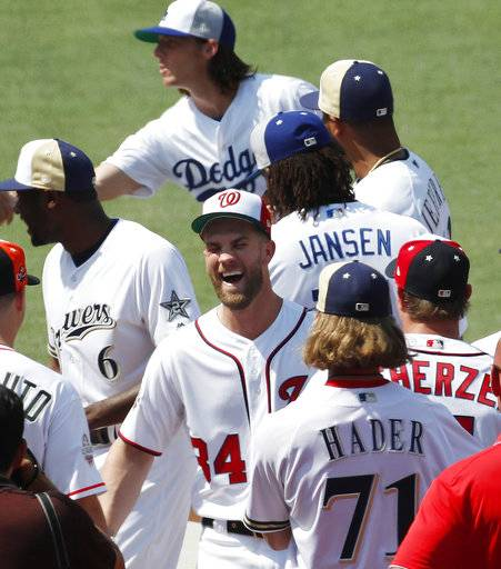 National League, Washington Nationals Bryce Harper, center, smiles as players mingle during a team photo, Monday, July 16, 2018, at Nationals Park, in Washington. The the 89th MLB baseball All-Star Game will be played Tuesday.