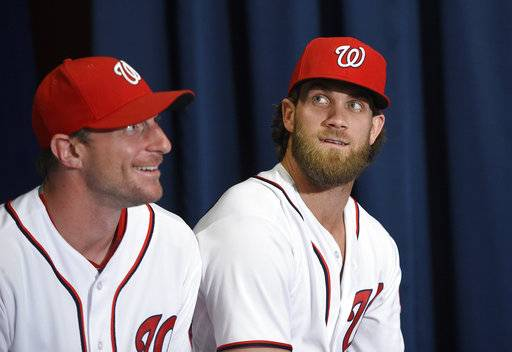 FILE - In this July 26, 2017, file photo, Washington Nationals' Max Scherzer, left, and Bryce Harper look on at a baseball press conference to unveil the 2018 MLB All-Star Game logo, in Washington. Thirteen years after Major League Baseball returned to Washington and almost that long since Mark and father Ted Lerner were chosen as owners of their new hometown team, they finally get to throw their party. The fourth All-Star Game in the nation's capital and first since 1969 is a celebration of a new generation of Washingtonians rediscovering the connection to baseball that for so long wasn't a part of the town's sporting identity.