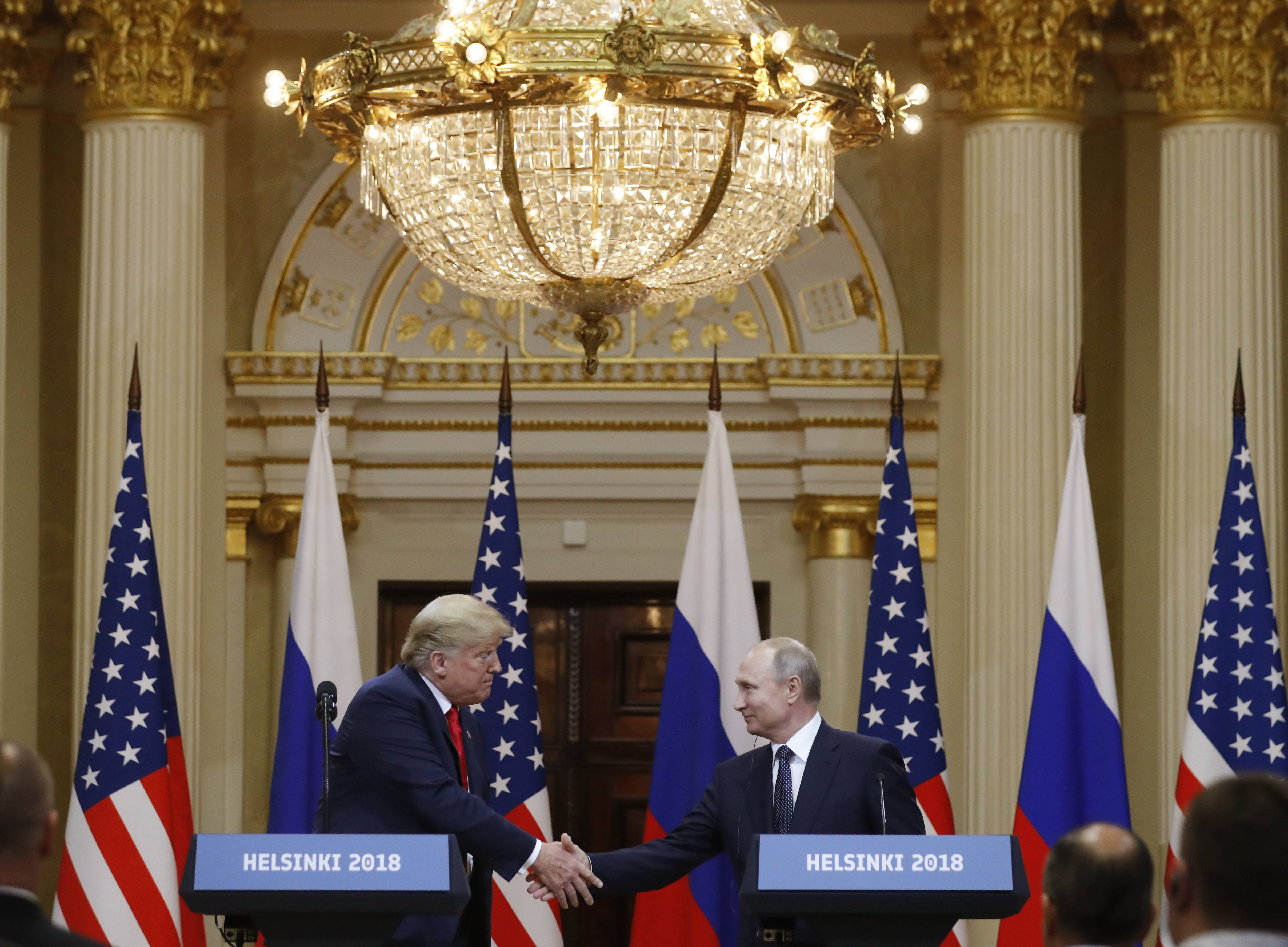 U.S. President Donald Trump, left, shakes hands MOnday with Russian President Vladimir Putin during a press conference after their meeting at the Presidential Palace in Helsinki, Finland.
