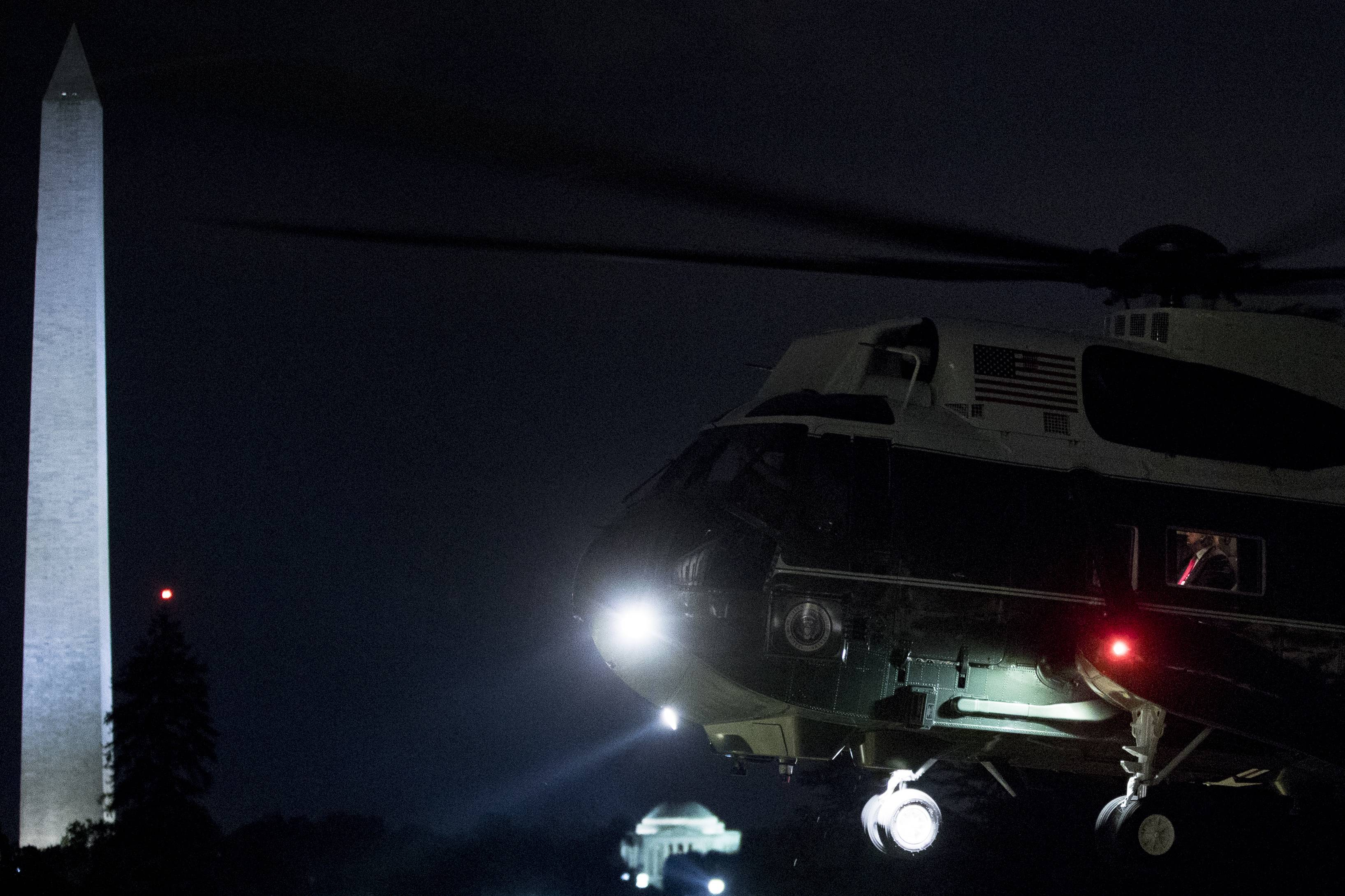 President Donald Trump with his red tie is visible in the window of Marine One Monday as it touches down on the South Lawn of the White House in Washington.