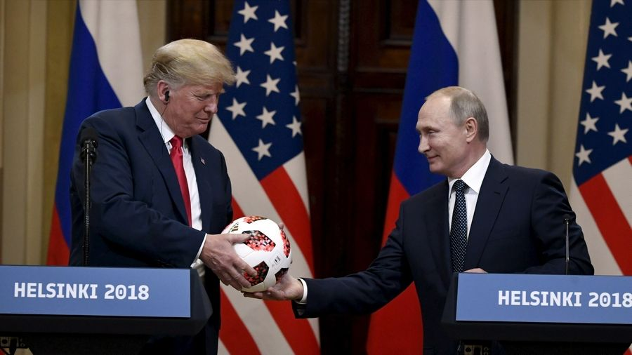 Russian President Vladimir Putin presents a World Cup soccer ball to President Donald Trump during a joint news conference in Helsinki, Finland, on Monday that drew ire from American lawmakers.