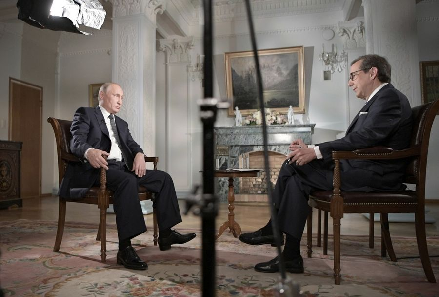 "Russian President Vladimir Putin, left, gestures Monday during an interview with ""Fox News Sunday"" host Chris Wallace after his meeting with U.S. President Donald Trump in Helsinki, Finland."