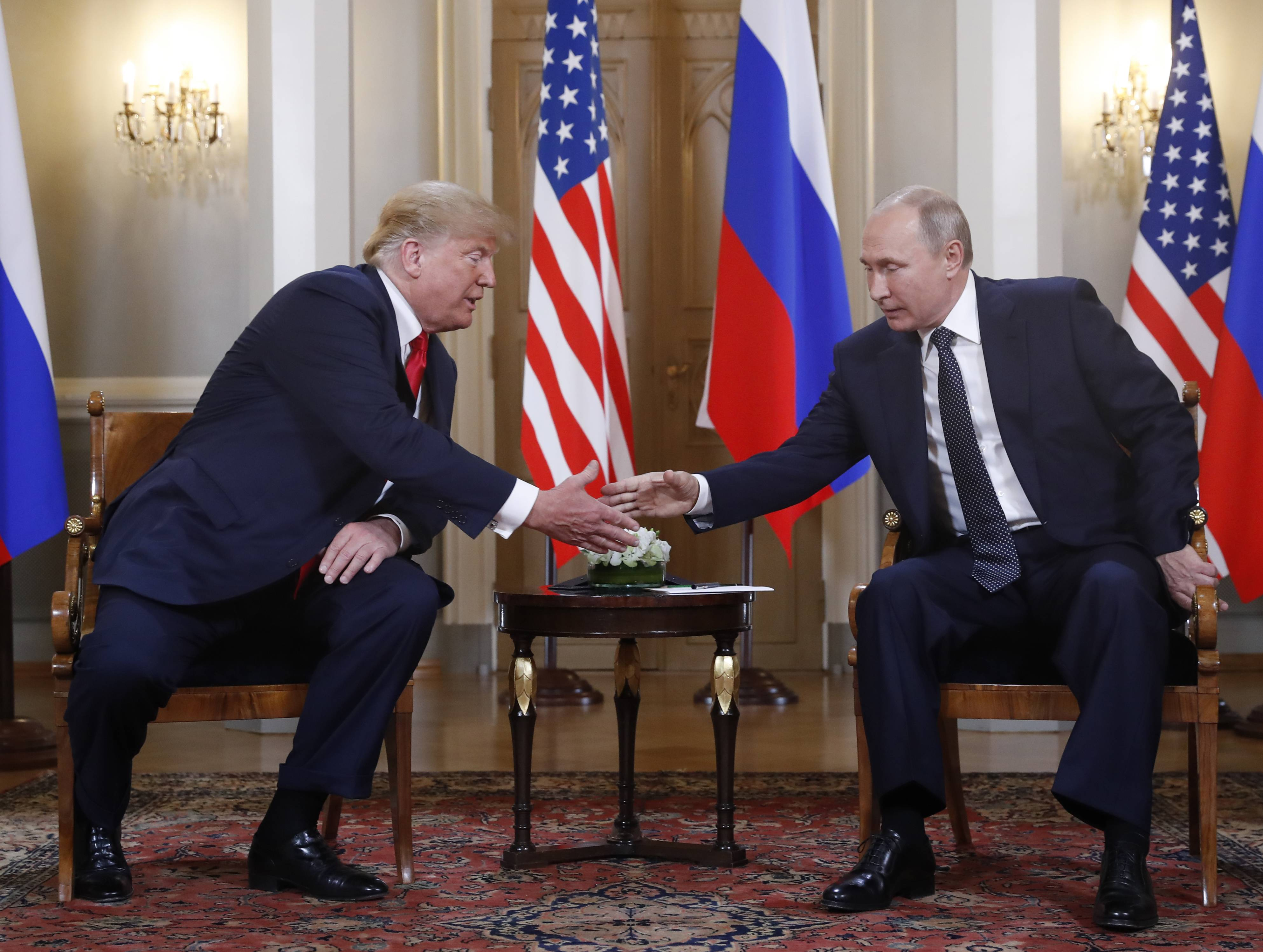 U.S. President Donald Trump, left, and Russian President Vladimir Putin shake hands Monday at the beginning of a meeting at the Presidential Palace in Helsinki, Finland.