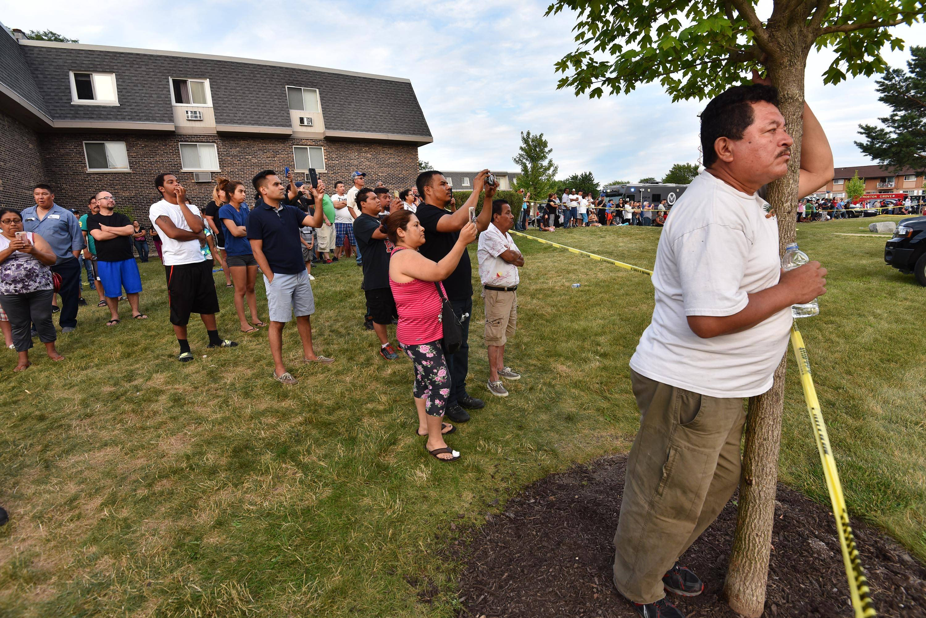 Residents and neighbors watch as firefighters continue to douse the fire at the River Trail condominiums Wednesday evening, seven hours after the fire started.