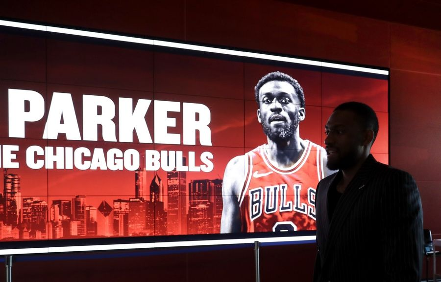 Jabari Parker walks in silhouette inside the United Center atrium past a signs welcoming him to the Chicago before a news conference where he was introduced as the newest member of the Bulls Wednesday, July 18, 2018, in his hometown of Chicago.