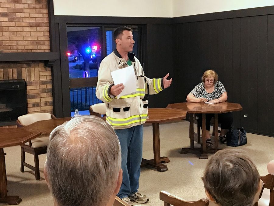 Mount Prospect Fire Chief Brian Lambel addresses residents in the clubhouse of an apartment complex on Yarmouth Place after a fire damaged at least five units and displaced residents Friday.