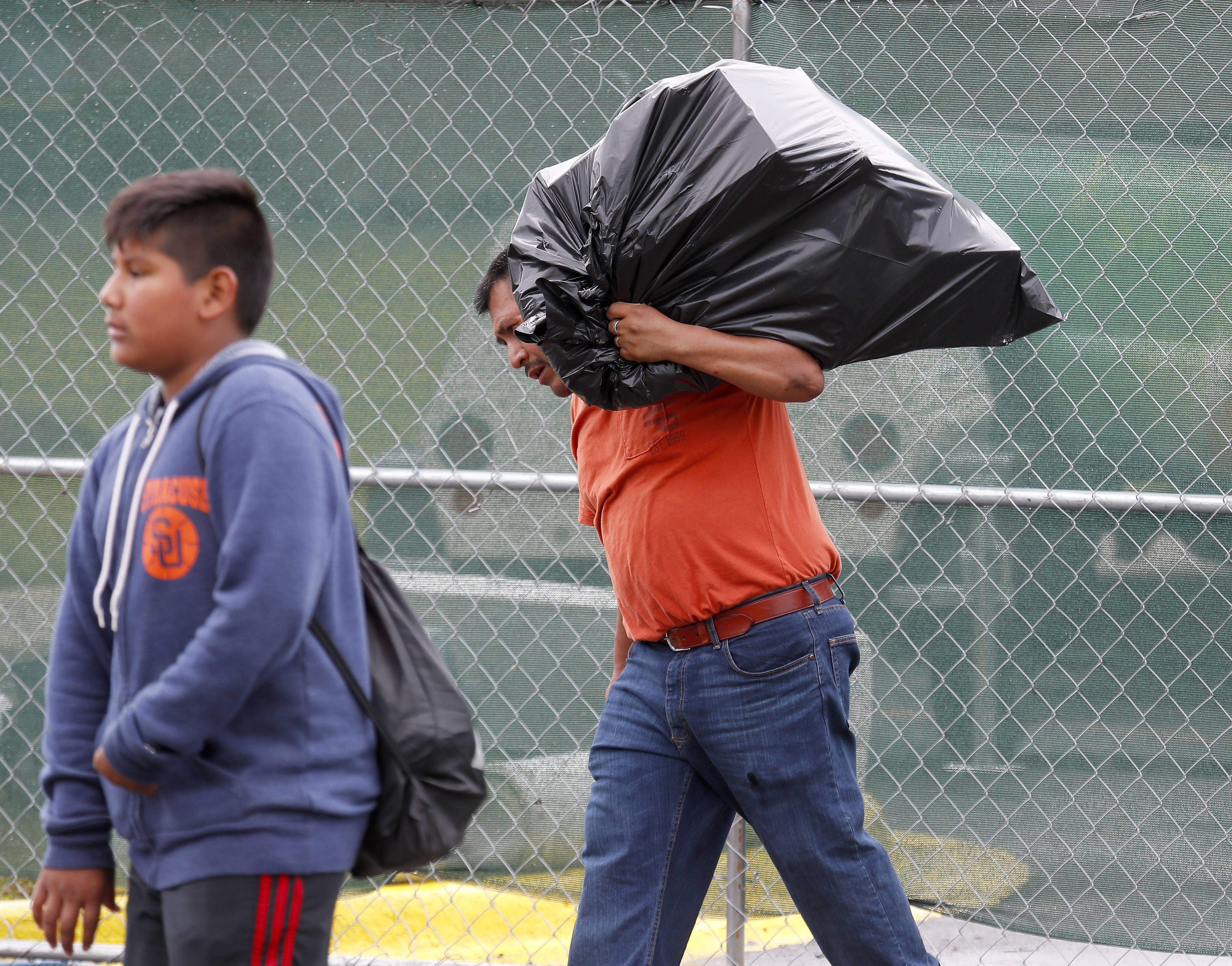 Rodrigo Pantoja, right, and his son David, 12, carry some of their belongings from the scene of a large fire at River Trails condominium complex in Prospect Heights. Pantoja has lived there for more than 20 years.
