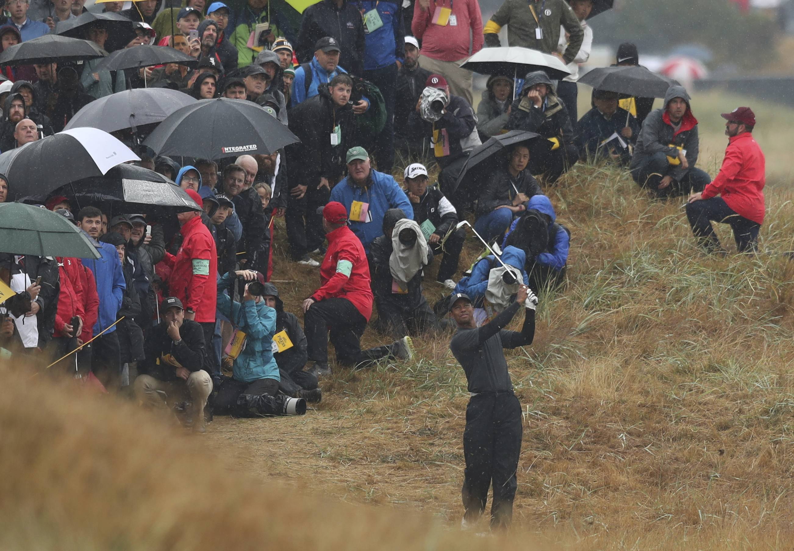 Tiger Woods plays out of the rough on the second hole Friday during the second round of the British Open Golf Championship in Carnoustie, Scotland.
