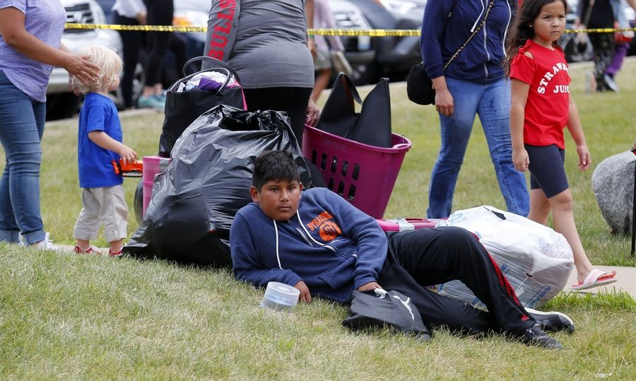 David Pantoja, 12, sits with his family's belongings at the site of a large fire at River Trails condominium complex in Prospect Heights.