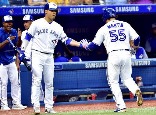 Toronto Blue Jays' Aledmys Diaz, front left, congratulates teammate Russell Martin (55) after Martin's solo home run during fifth-inning baseball game action against the Baltimore Orioles in Toronto, Friday, July 20, 2018. (Frank Gunn/The Canadian Press via AP)