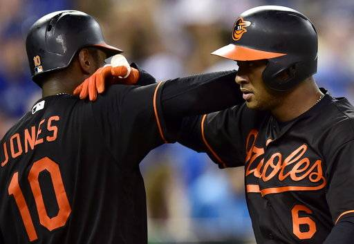 Baltimore Orioles' Jonathan Schoop (6) celebrates with teammate Adam Jones (10) after his home run during ninth-inning baseball game action against the Toronto Blue Jays in Toronto, Friday, July 20, 2018. (Frank Gunn/The Canadian Press via AP)