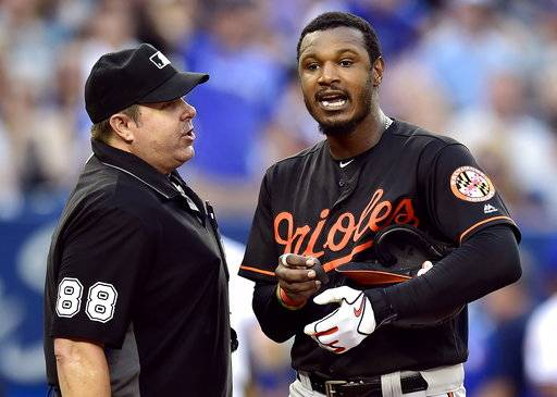 Baltimore Orioles' Adam Jones, right, has words for umpire Doug Eddings (88) during fifth-inning baseball game action against the Toronto Blue Jays in Toronto, Friday, July 20, 2018. (Frank Gunn/The Canadian Press via AP)