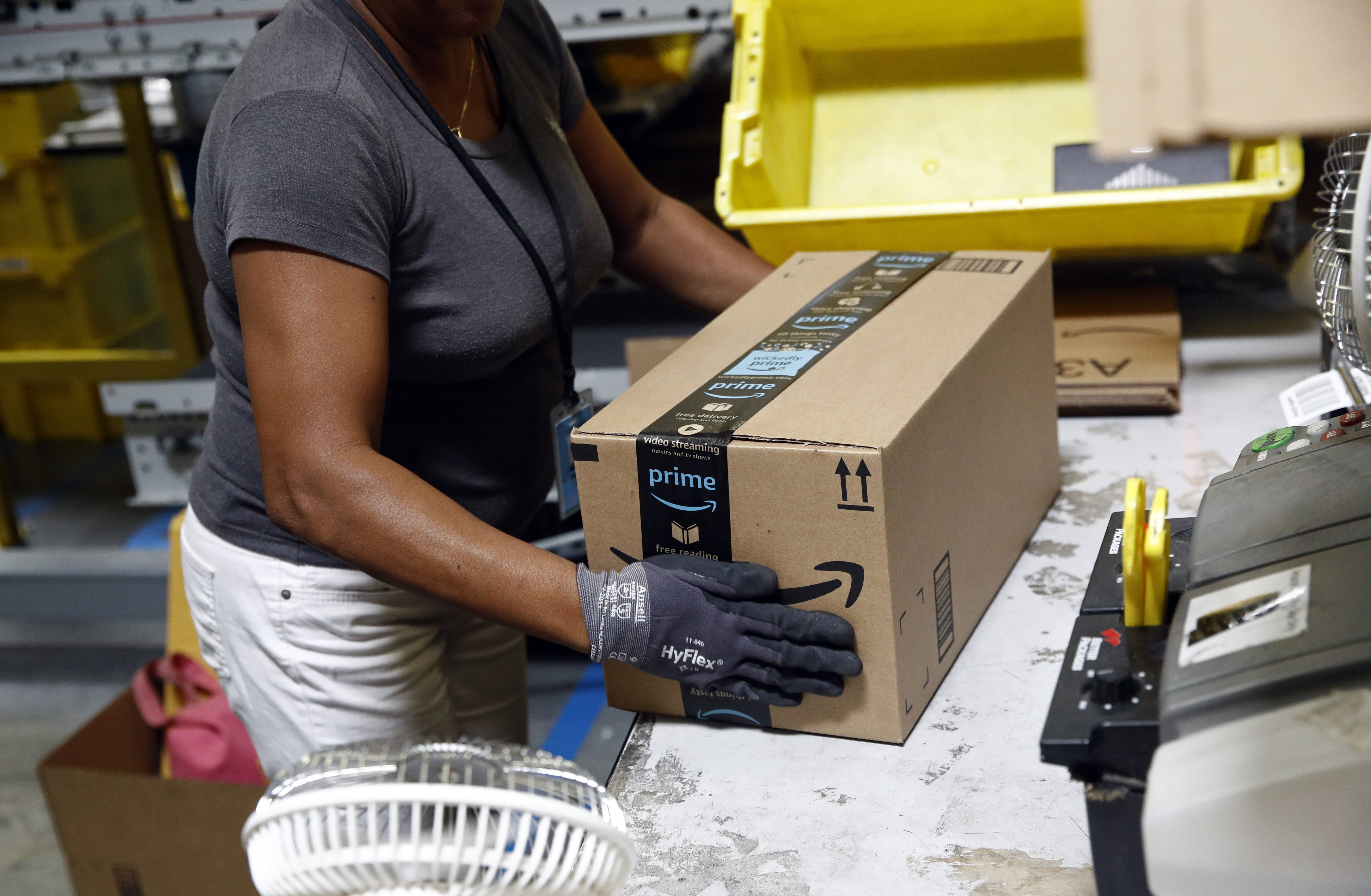 Myrtice Harris applies tape to a package before shipment at an Amazon fulfillment center in Baltimore. Amazon's Prime Day starts July 16, 2018, and will be six hours longer than last year's and will launch new products.