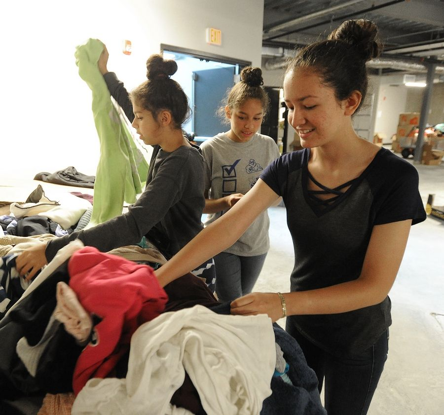 Leslie Gonzalez, 15, right, with the help of her best friends Kayleen, 13, and Nicole Golden, 15, picks out donated clothes Saturday for herself and her sister Princess at The Bridge Community Church in Prospect Heights. Leslie's family is among 95 families displaced by Wednesday's fire in Prospect Heights.