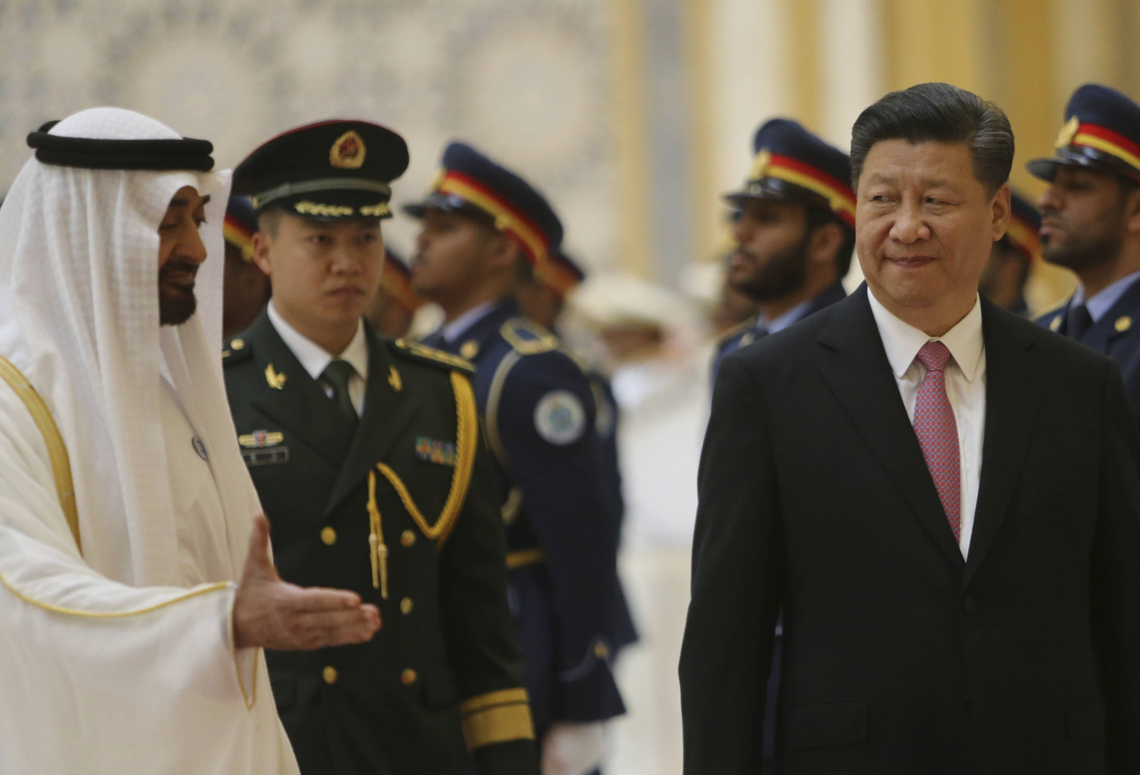 Sheikh Mohamed bin Zayed Al Nahyan, Crown Prince of Abu Dhabi, left, gestures Friday to Chinese President Xi Jinping, right, with Deputy Supreme Commander of the UAE Armed Forces, second left after reviewing the Guard of Honour, at the Presidential Palace in Abu Dhabi, United Arab Emirates.