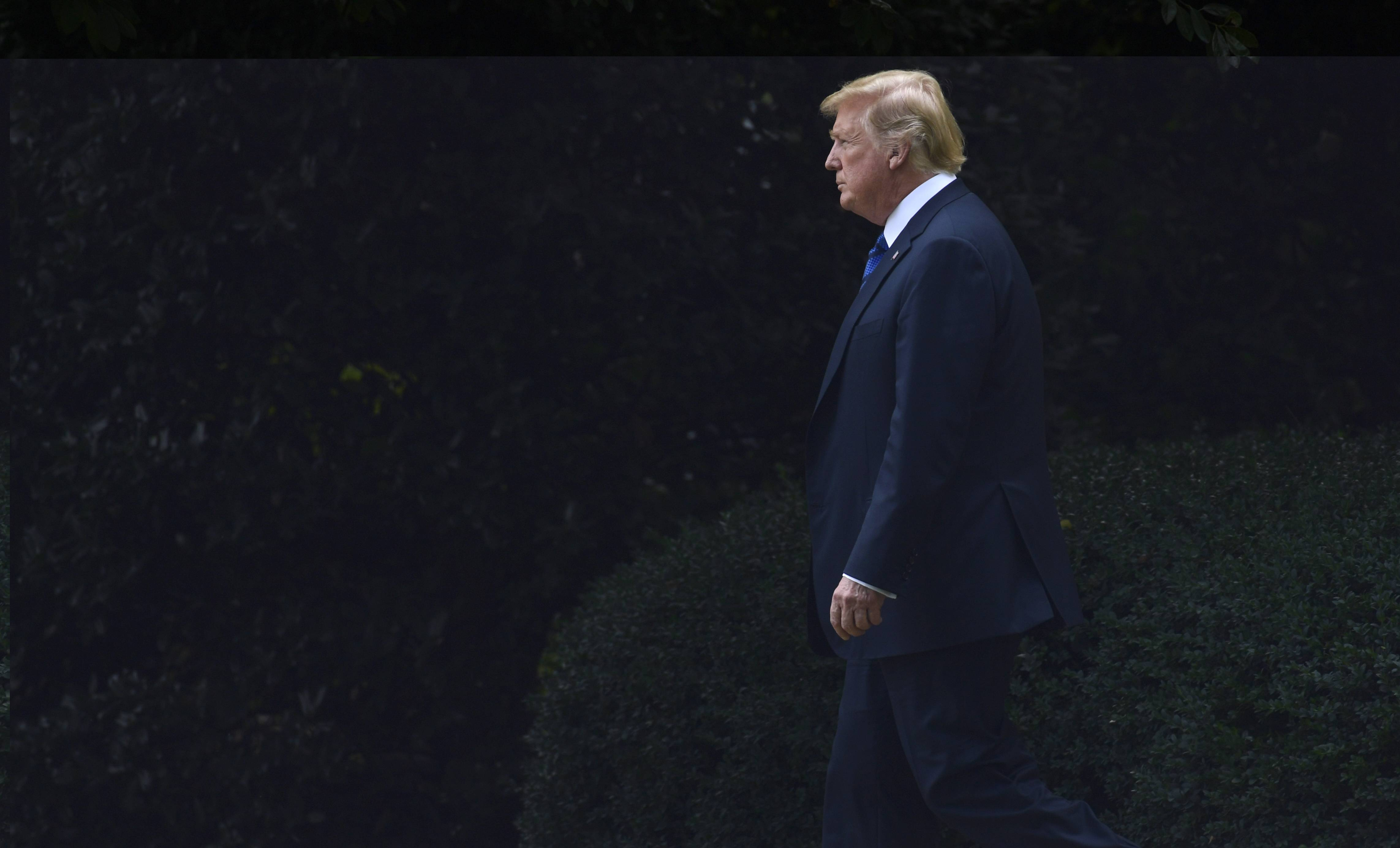 President Donald Trump walks from the Oval Office of the White House to board Marine One for a short trip to Andrews Air Force Base, Maryland, en route to Bedminster, New Jersey, for the weekend.