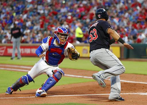 Cleveland Indians' Melky Cabrera (53) avoids a tag by Texas Rangers catcher Robinson Chirinos, left, to score on a single hit by teammate Yan Gomes during the fifth inning of a baseball game, Saturday, July 21, 2018, in Arlington, Texas.
