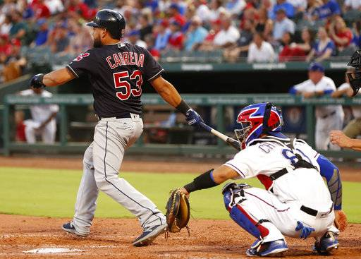 Cleveland Indians' Melky Cabrera (53) follows through on a double in front of Texas Rangers catcher Robinson Chirinos, right, during the fifth inning of a baseball game, Saturday, July 21, 2018, in Arlington, Texas.